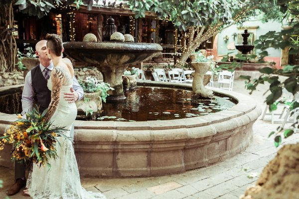 BRIDE AND GROOM KISSING ON A FOUNTAIN