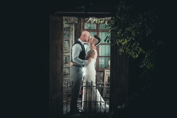 BRIDE AND GROOM KISSING THROUGH A DOORWAY