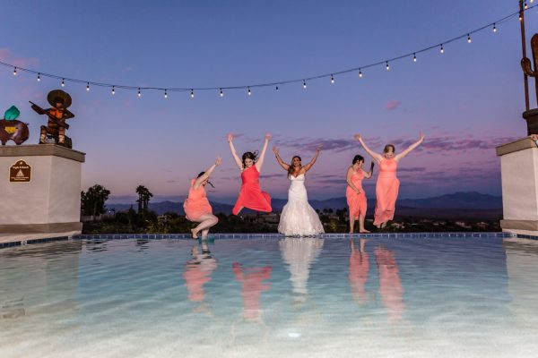 brides jumping into pool at wedding